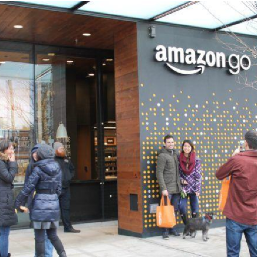 A handful of people standing in front of a Amazon Go wall